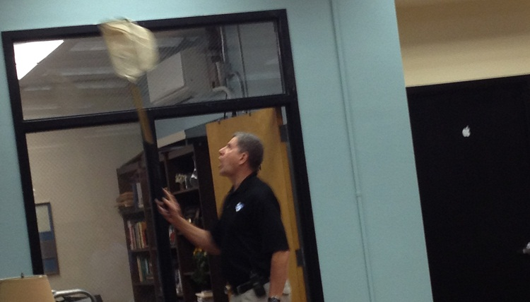 Security guard Al Maas trying to catch the bird in the Library Media Center.