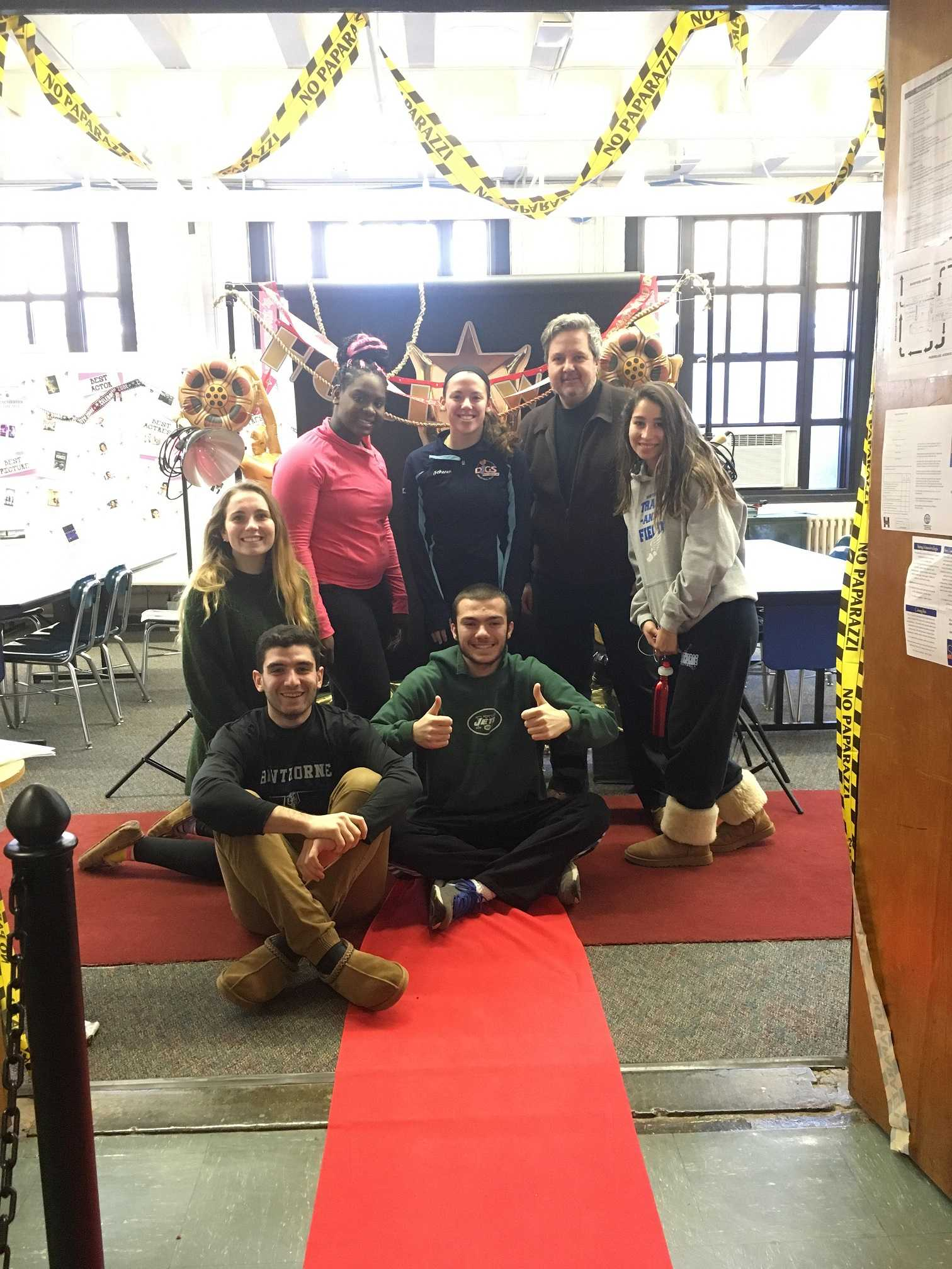 Advanced Media Arts students and Student Council president pose on the red carpet with Media Arts teacher John DiLonardo