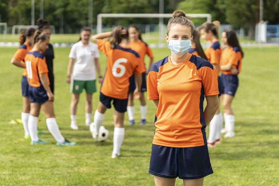 Young female soccer player wearing protective face mask on the field.