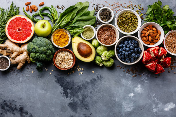 Healthy+food+clean+eating+selection%3A+fruit%2C+vegetable%2C+seeds%2C+superfood%2C+cereals%2C+leaf+vegetable+on+gray+concrete+background+copy+space