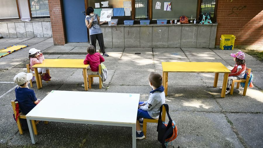 IVREA, TURIN, ITALY - 2020/05/26: A teacher reads a book to kindergarten children in a school garden. Municipality of Ivrea opens the gardens of two kindergarten schools as part of a pilot test to see how schools can reopen after COVID-19 coronavirus lockdown. (Photo by Nicolò Campo/LightRocket via Getty Images)