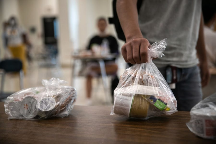 STAMFORD, CONNECTICUT - SEPTEMBER 08: A student picks up a free individually bagged lunch in the cafeteria during the first day of school at Stamford High School on September 08, 2020 in Stamford, Connecticut. Due to the coronavirus pandemic, many school districts nationwide delayed the first day of school until after the Labor Day weekend. Stamford Public Schools started the semester with a hybrid model, which includes in-class learning every other day. Many families, however, chose the distance learning option due to fears of COVID-19 transmission between students. (Photo by John Moore/Getty Images)